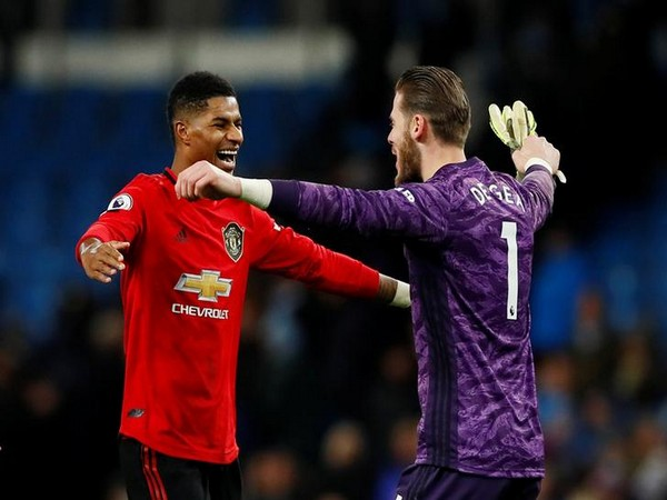 Marcus Rashford celebrates with David de Gea after winning against Manchester City
